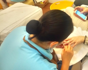 Nailaholics worker giving a manicure to one of their regular customer.